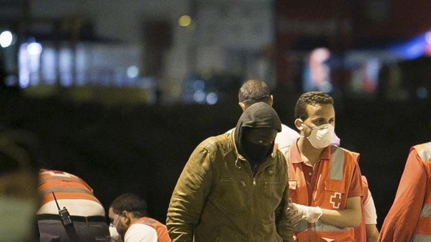 Miembros de la cruz roja ayudan a uno de los 43 inmigrantes subsaharianos rescatados por Salvamento Marítimo, a su llegada al puerto del Rosario en Fuerteventura, cuando navegaban en una patera localizada a 79 millas (146 kilómetros) al este de la isla. EFE / Gabriel Fuselli.