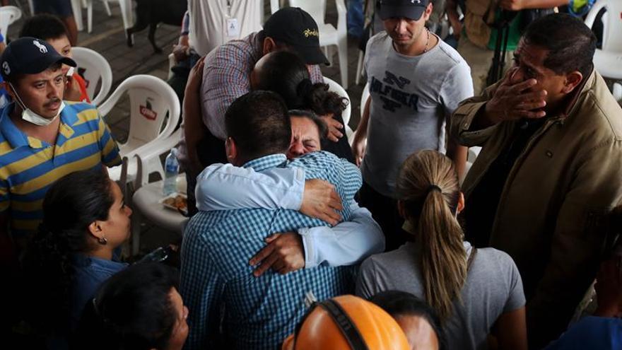 Un grupo familiares de víctimas de la erupción del Volcán de Fuego se abraza junto a varios socorristas este lunes 4 de junio de 2018, en Alotenango (Guatemala).