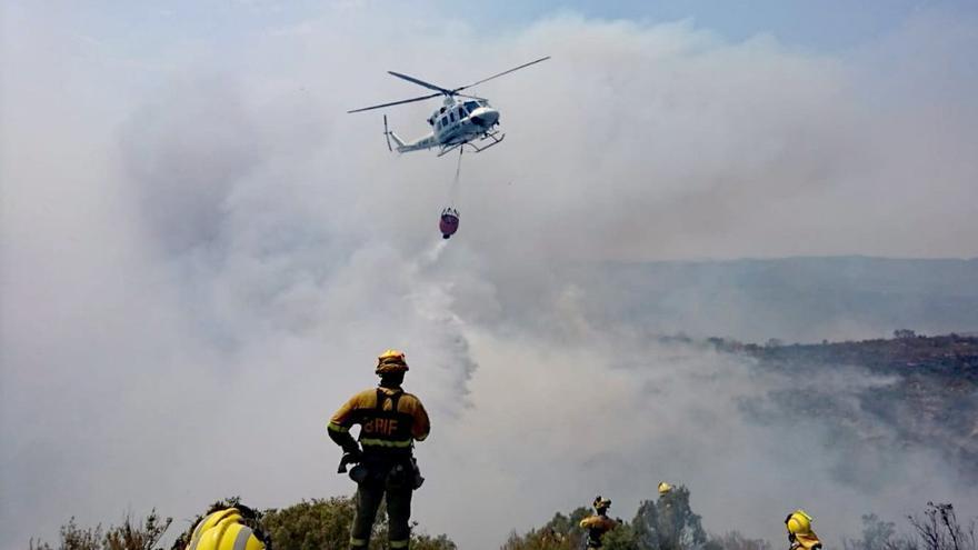 Un helicóptero descarga sobre la zona afectada por el incendio de Llutxent ante la mirada de un bombero forestal