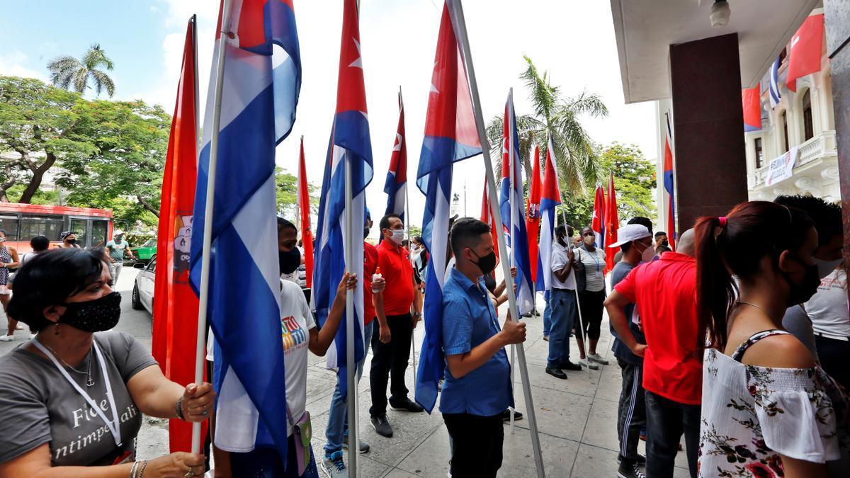 Varias personas con banderas cubanas permanecen fuera de la sede nacional de la Unión de Jóvenes Comunistas (UJC), en La Habana.
