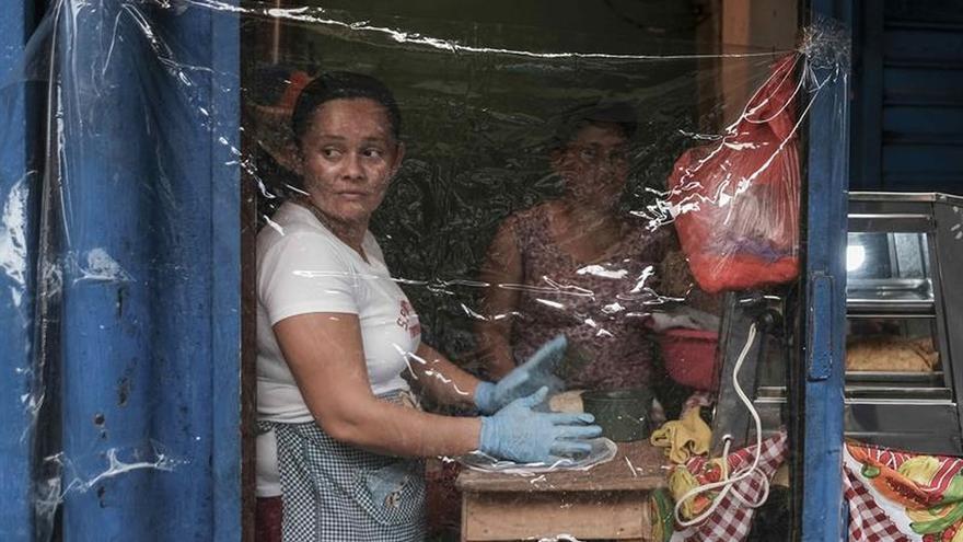 Varios vendedores forran sus locales con plásticos para proteger de la COVID-19, este martes, en San José, Costa Rica.