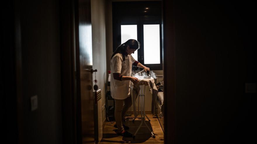 Una empleada doméstica planchando en un hogar en España.