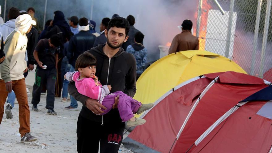 Un hombre sostiene a su hijo mientras arden restos de basura detrás en Lesbos, Grecia © Petros Tsakmakis/InTime News via AP