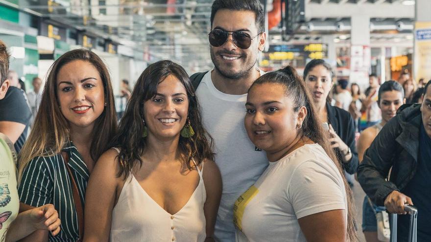 Carlos Rivera con tres fans en el aeropuerto.