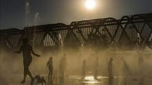 Varias personas se refrescan en las fuentes de Madrid Río. / Efe
