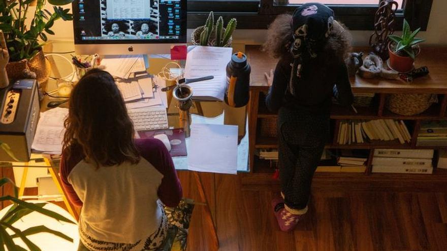 Una mujer realiza teletrabajo en su casa mientras su hija juega a su lado.