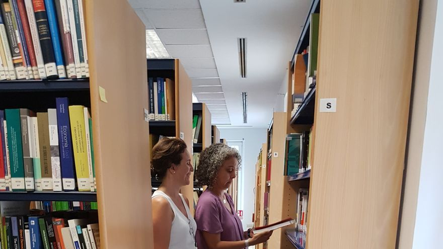 Amparo y Teresa, responsables de la biblioteca de les Corts, hojean los nuevos ejemplares