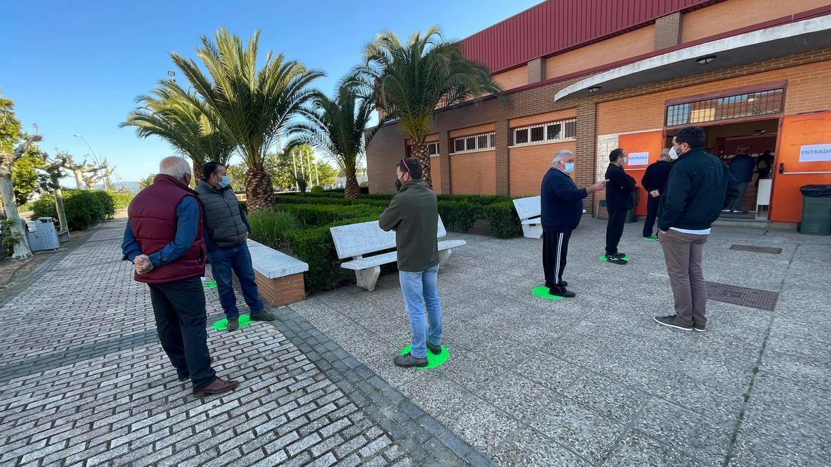 Varias personas esperan en la puerta del polideportivo de Navalvillar de Pela para hacerse una prueba de covid por el brote de los esquiladores