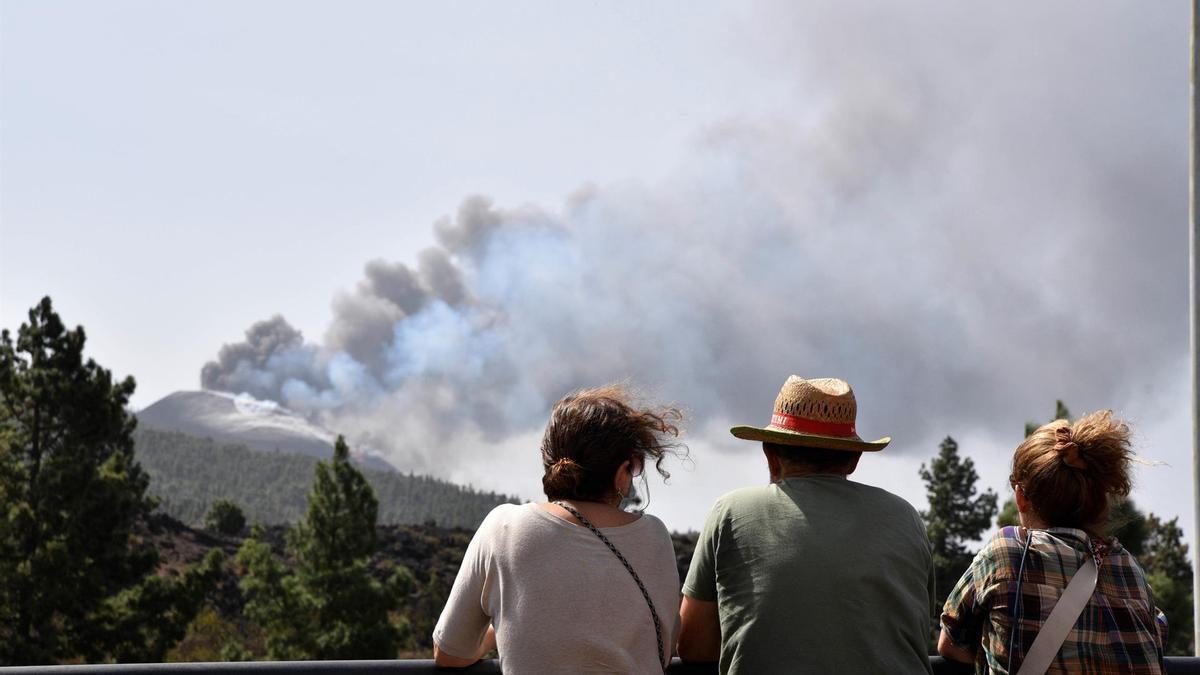 Varias personas observan el volcán de Cumbre Vieja que este sábado continúa su actividad, registrando una intensa emisión de gases a través de un amplio campo de fumarolas. EFE/MIGUEL CALERO