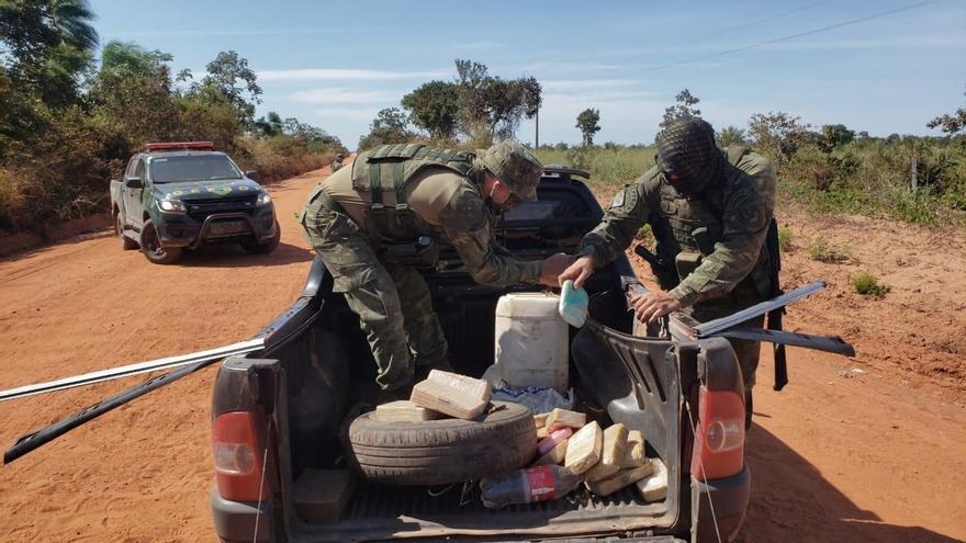 Fotografía sin fecha cedida por la Policía Militar del estado de Mato Grosso (Brasil), que muestra a integrantes de las fuerzas de seguridad mientras revisan un cargamento de drogas en Brasil.