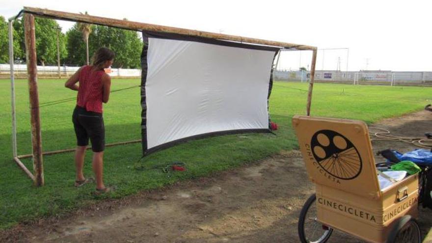 Isabel monta la pantalla para la proyección