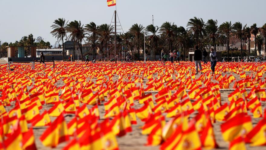 """La playa de La Patacona del municipio valenciano de Alboraya ha amanecido este domingo con 53.000 banderas de España, colocadas en la arena durante esta madrugada por voluntarios de la Asociación Nacional de Víctimas y Afectados por Coronavirus (Anvac), en homenaje a las personas fallecidas por la covid-19 desde el inicio de la pandemia y """"rendirles un emotivo acto de recuerdo"""". EFE/Manuel Bruque"""