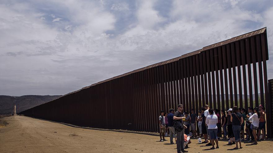 Activistas de Border Angels frente al Muro entre México y EEUU. | José Pedro Martínez
