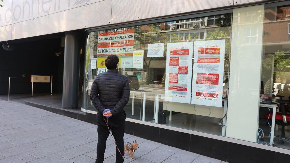 Un hombre lee los avisos informativos de una oficina de Empleo.