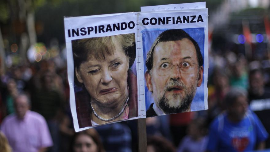 "Protestors hold a banner with a photo of German Prime Minister Angela Merkel and Spanish Prime Minister Mariano Rajoy reading ""inspiring confidence"" as they march against healthcare austerity measures announced by the Spanish government in Madrid, Spain, Saturday, Oct. 6, 2012."