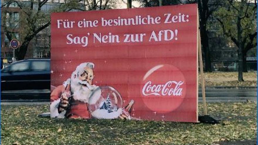 Pancarta con un anuncio de Coca-Cola con un lema anti AfD