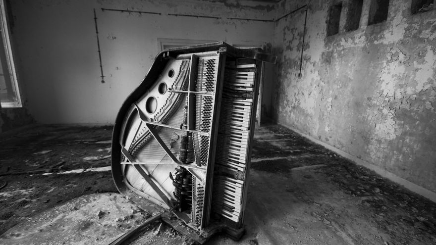 El piano de otra clase de música de la escuela en Prípiat, volcado y con su interior al descubierto