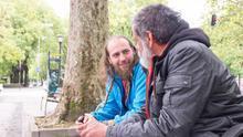 El educador de calle Arkaitz Ulayar conversa con Imanol Montero, que vive en un cajero.