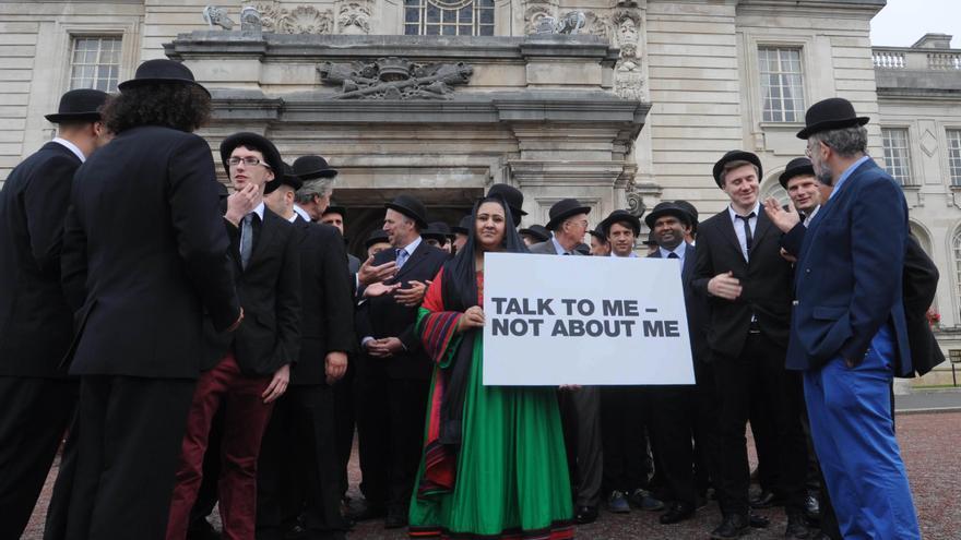 La abogada por los derechos de las mujeres, Samira Hamidi, rodeada de hombres, sujeta un cartel de protesta en el ayuntamiento de Cardiff © PA
