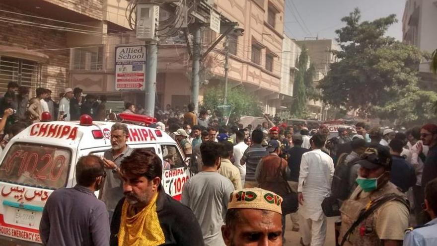 Una ambulancia intenta acceder a las inmediaciones del lugar en el que se ha producido el siniestro en Karachi, Pakistán.