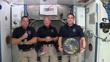 Captura del video de la NASA donde aparecen los astronautas de la NASA Chris Cassidy (d) y el comandante Douglas Hurley (c) mientras escuchan a Robert L. Behnken (i) este lunes en la Estación Espacial Internacional (EEI).