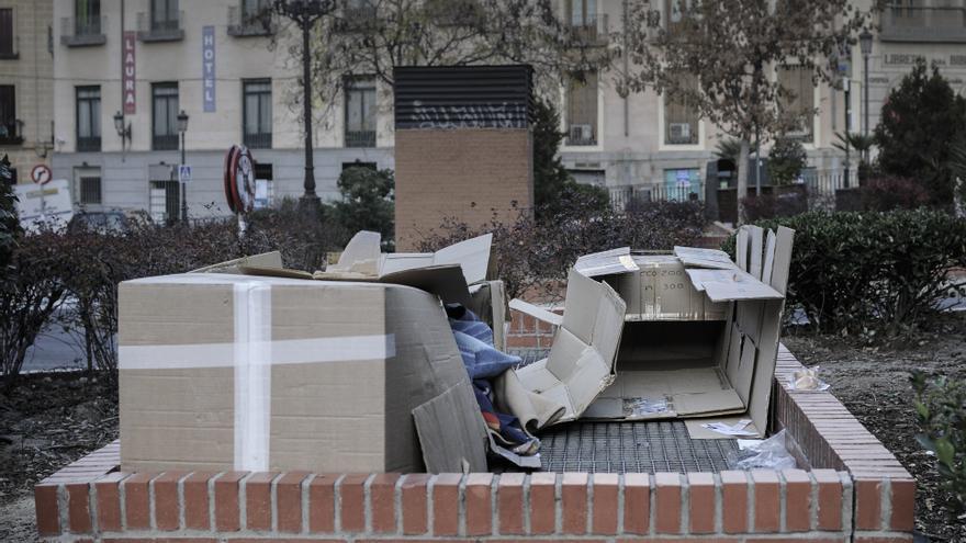Una persona sin hogar, entre cartones.