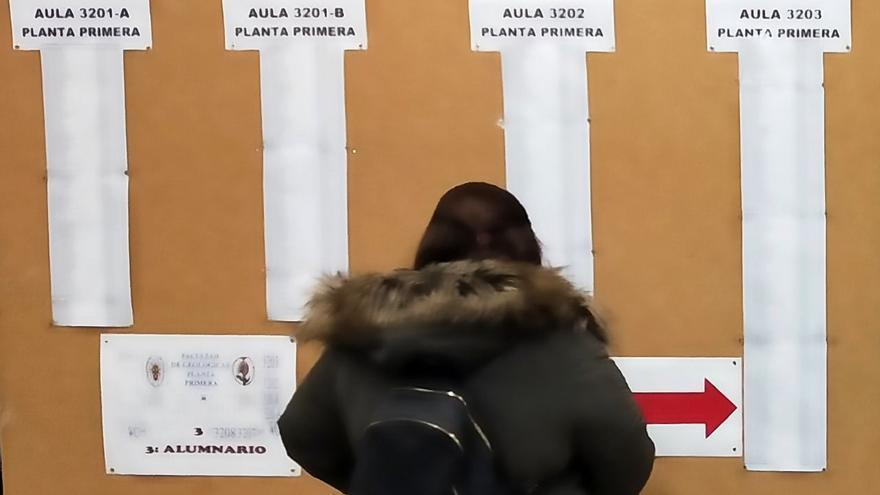 Una mujer consulta una cartelera con nombres en la facultad de Biología de la Universidad Complutense de Madrid, este domingo
