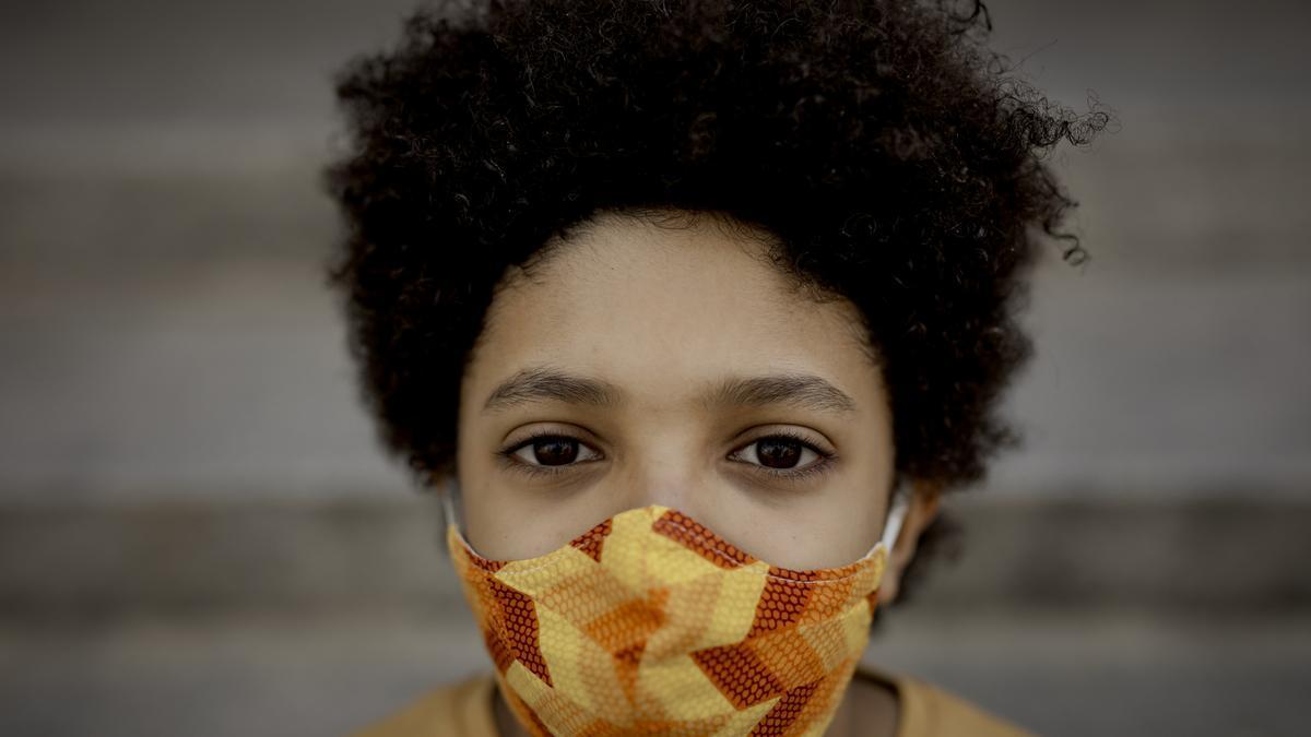 Un niño pasea por Madrid con una mascarilla puesta por la epidemia de coronavirus.