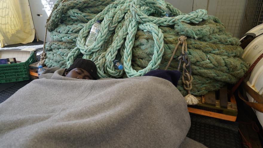 Dos hombres descansan en el interior del Sea Watch 3.