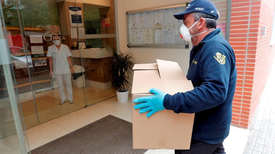 Un miembro de protección civil entrega material sanitario comprado en China en una residencia.