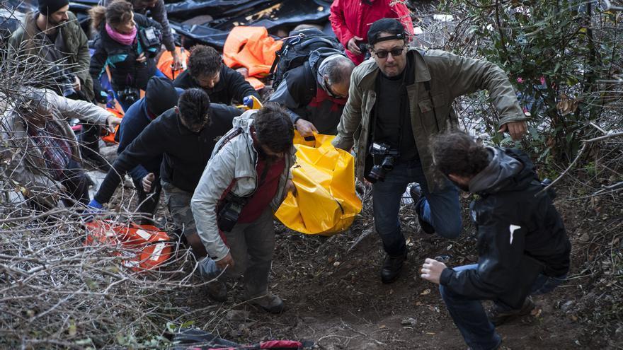 Un grupo de fotógrafos trasladan el cadáver de un refugiado en una playa del norte de Lesbos, Grecia