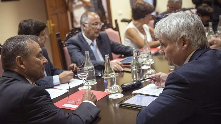 El presidente del Gobierno regional, Paulino Rivero, conversa con el vicepresidente José Miguel Pérez al comienzo del Consejo de Gobierno de Canarias. (EFE)
