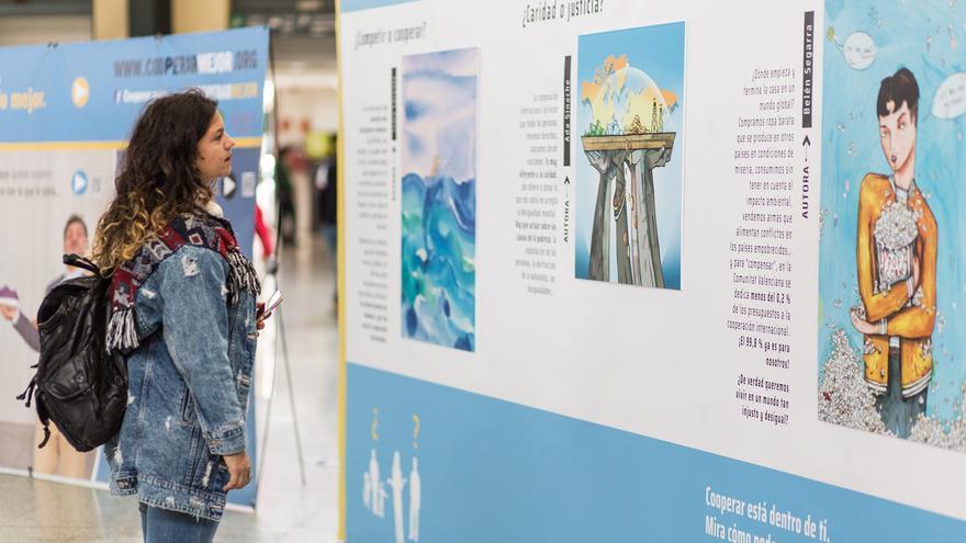 Una chica mira las ilustraciones de la exposición