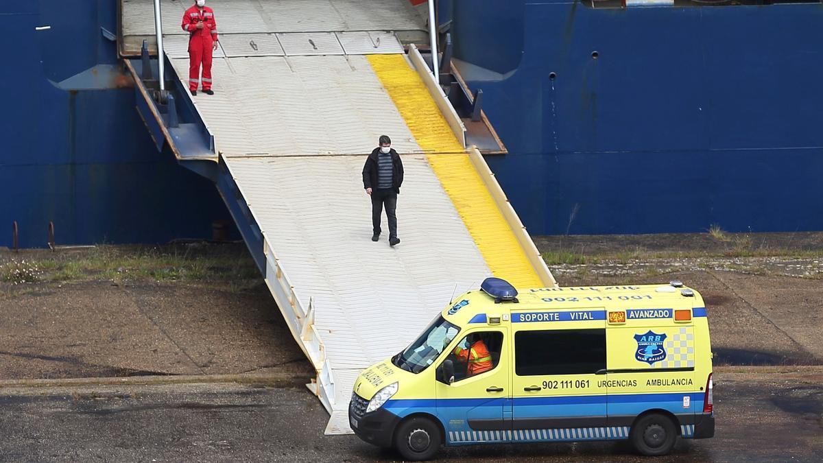 Una ambulancia espera a un hombre que desciende del 'Emerald Leader', en cuarentena en el puerto de Vigo por un brote de COVID-19
