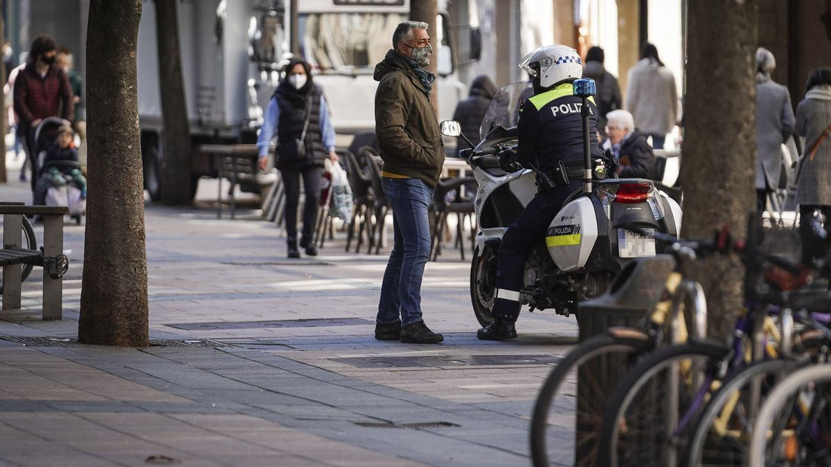 Un hombre habla con un policía local en una calle céntrica de Vitoria