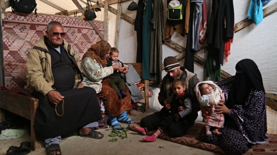 Jibril, a la izquierda, perdió a dos de sus cuatro nietos por hipotermia en las tormentas del mes pasado. La familia ahora vive en una pequeña estructura de madera cubierta de plástico en Beit Hanoun con una manta por puerta. Fotografía: Belal Hasna