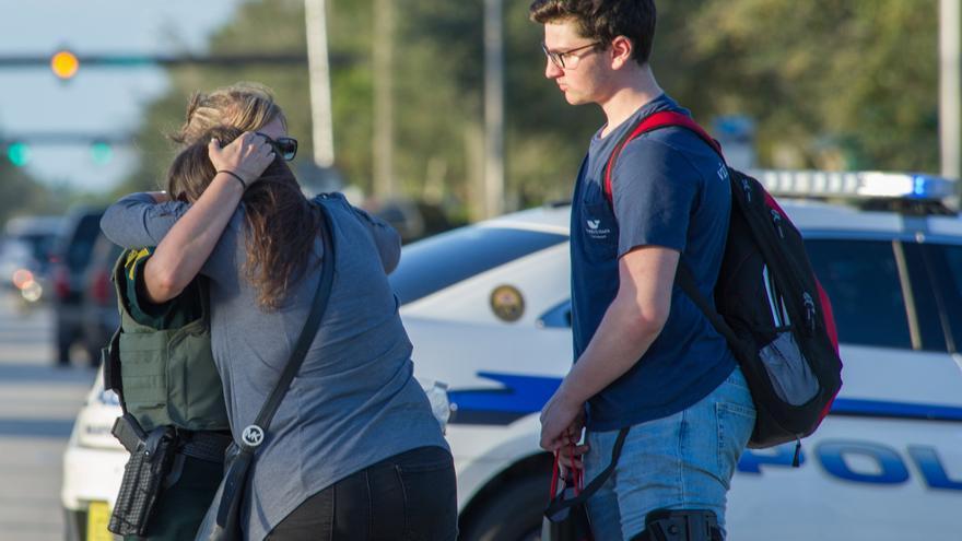 Una oficial de policía consuela a una mujer tras el tiroteo registrado hoy, miércoles 14 de febrero de 2018, en la escuela secundaria Marjory Stoneman Douglas de la ciudad de Parkland, en el sureste de Florida (Estados Unidos).