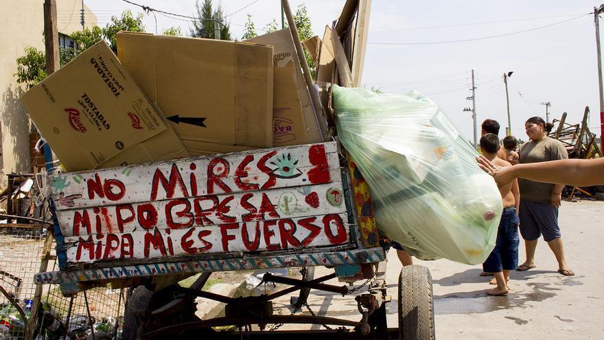 Menores juegan en torno al carro de un recolector de cartón en una calle de Buenos Aires.