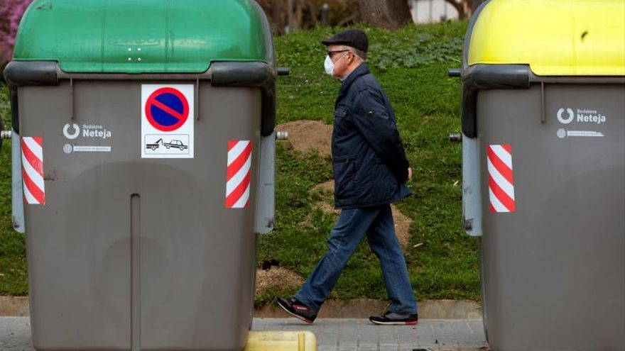 Un hombre con una mascarilla pasa cerca de unos contenedores de basura durante un paseo.