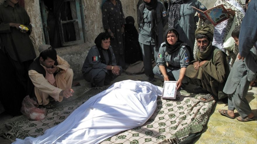 Mujeres policía afganas y familiares de la víctima, junto al cuerpo de la mujer policía asesinada por hombres desconocidos en la provincia de Helmand, Afganistán, en septiembre de 2013 © STR/AFP/Getty Images