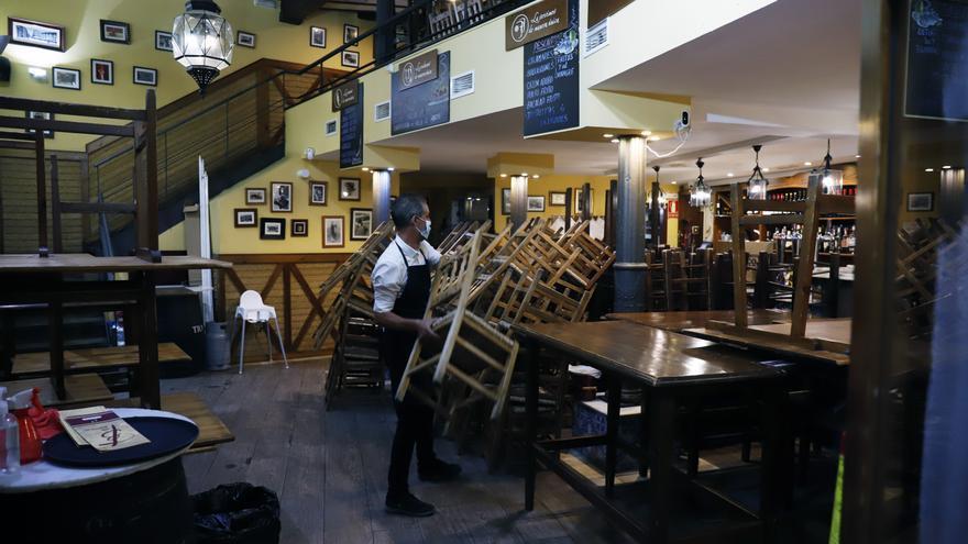 Un camarero recoge en el interior de un bar.