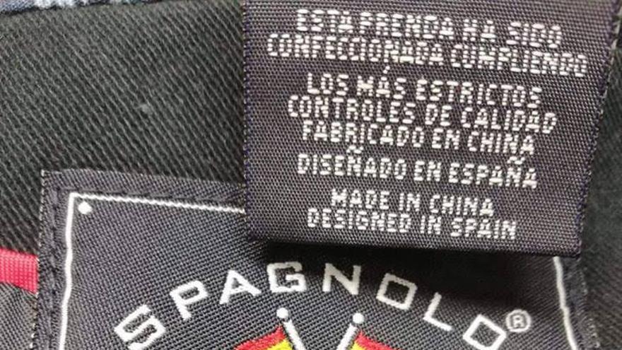 b8784eff4a63 Etiqueta de la marca Spagnolo con dos banderas españolas cruzadas y su lema