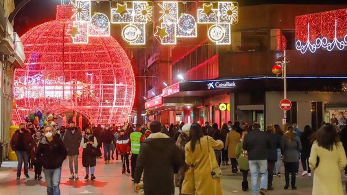 Transeúntes pasean bajo las luces navideñas en Vigo en diciembre de 2020.