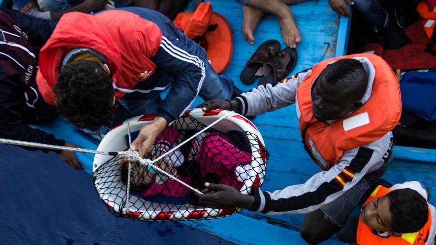 Los equipos de rescate del Bourbon Argos elevan a un bebé desde la cubierta de una precaria embarcación de madera. Según ACNUR, a finales de 2015, la mitad de los refugiados en todo el mundo eran niños. Fotografía: Borja Ruiz Rodriguez/MSF.