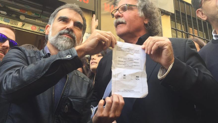 Joan Tardá (ERC) y Jordi Cuixart, presidente de Omnia Cultural, sostienen una papeleta del 1-O en el Teatro del Barrio.