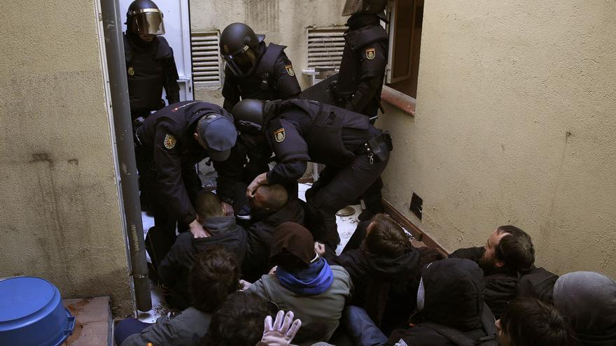 Varios policías antidisturbios levantando de forma violenta a los activistas antidesahucios