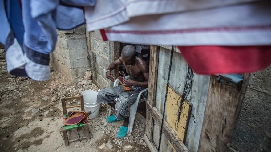 Un zapatero trabaja ante su casa en República Dominicana.