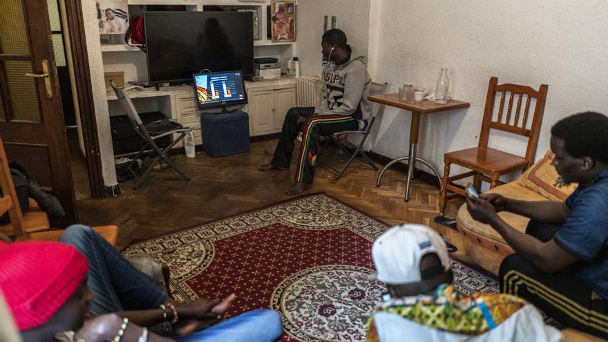 Varios ciudadanos senegaleses, dedicados a la venta ambulante, observan las noticias después de un mes del inicio del estado de alarma.