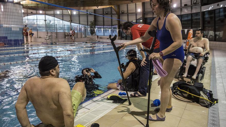 Paco (sentado en la piscina), junto a Carmen (de pie) y Juan Carlos (en su silla). / O. M.
