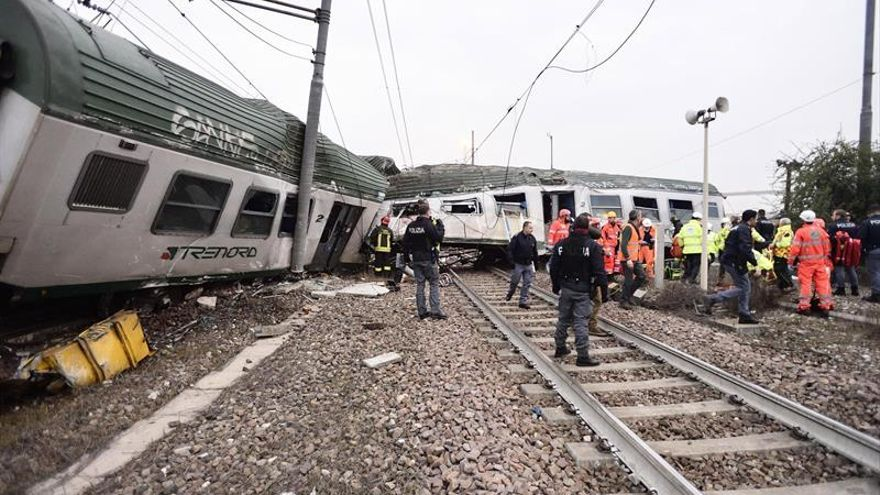 Miembros de los servicios de emergencia trabajan en el lugar del suceso después de que un tren descarrilara cerca de Milán (Italia).
